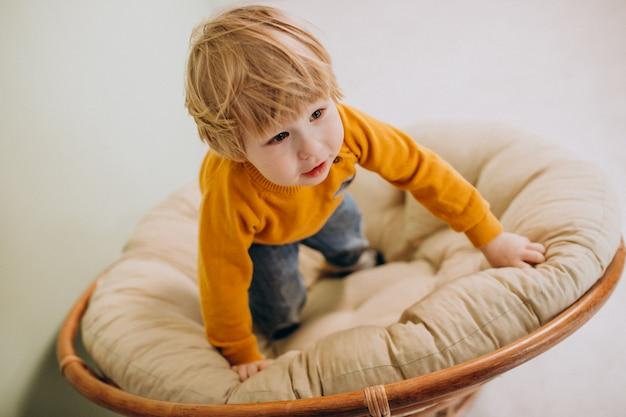 Kleiner netter junge, der in einem stuhl sitzt
