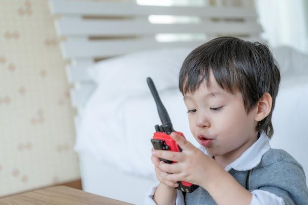 Kleiner netter junge, der zur unterhaltung mit rotem funksprechgerät redio im schlafzimmer genießt