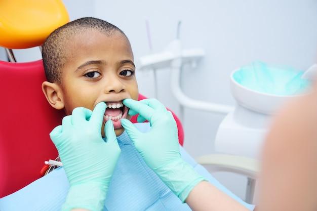 Kleiner netter schwarzer baby afroamerikaner, der im zahnmedizinischen stuhl sitzt.