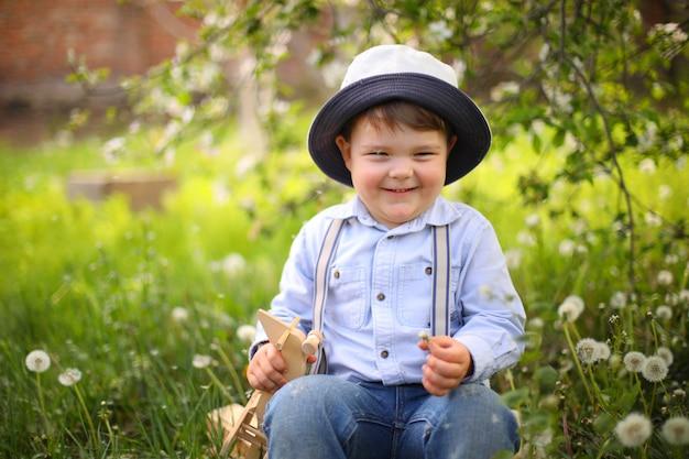 Kleiner niedlicher blonder junge, der mit einem hölzernen flugzeug im sommerpark auf dem gras an einem sonnigen tag spielt