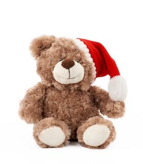 Kleiner niedlicher brauner teddybär mit in einem roten weihnachtshut sitzt