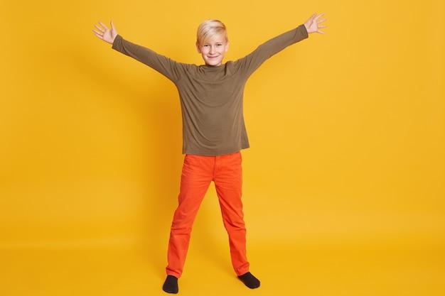 Kleiner niedlicher kinderjunge, der freizeitkleidung lokalisiert auf gelber wand, kinderporträt trägt. aufrichtige gefühle der menschen, lebensstilkonzept der kindheit, süßer kerl, der glück ausdrückt.