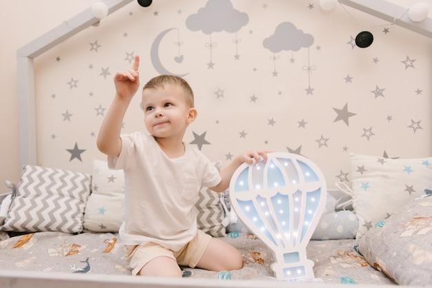 Kleiner niedlicher kleiner junge, der im kinderzimmer in einem hölzernen betthaus mit nachtlichtern in der form eines ballons sitzt