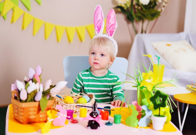 Kleiner niedlicher kleiner junge mit weißem haar mit hasenohren auf seinem kopf, der an einem tisch vor einem osterkorb und dekor sitzt.