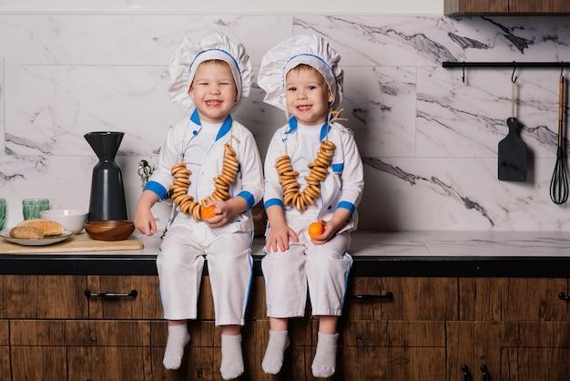 Kleiner niedlicher koch mit besteck, der auf einer küche sitzt