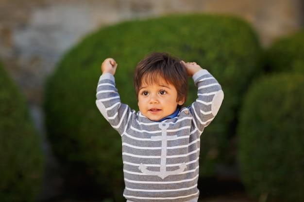 Kleiner östlicher hübscher junge, der mit kieselsteinen im freien im park spielt