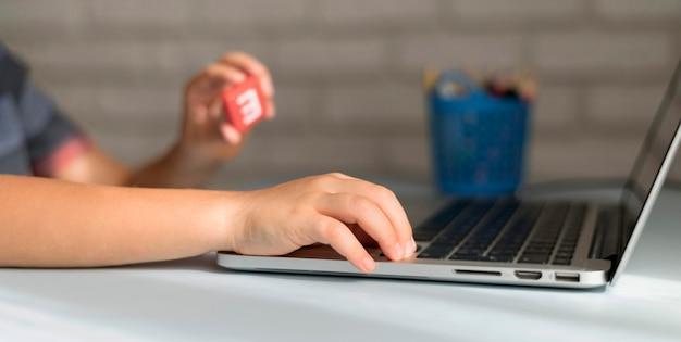 Kleiner online-student, der auf laptop schreibt