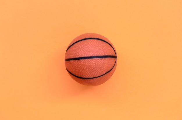 Kleiner orange ball für basketball-sportspiel liegt auf beschaffenheitspastellorange