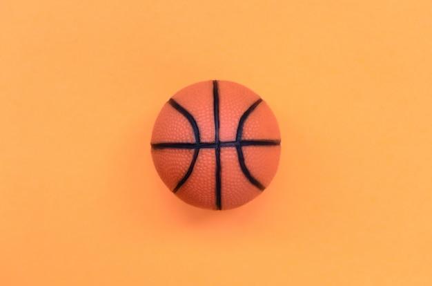 Kleiner orange ball für basketballsportspiel liegt auf beschaffenheitshintergrund des orange pastellfarbpapiers der mode im minimalen konzept