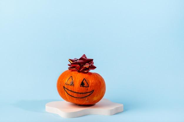 Kleiner orange geschnitzter kürbis auf blauem hintergrund mit kopienraum. konzeptfeier von halloween oder thanksgiving. kosmetik-podest für halloween. herbststillleben.