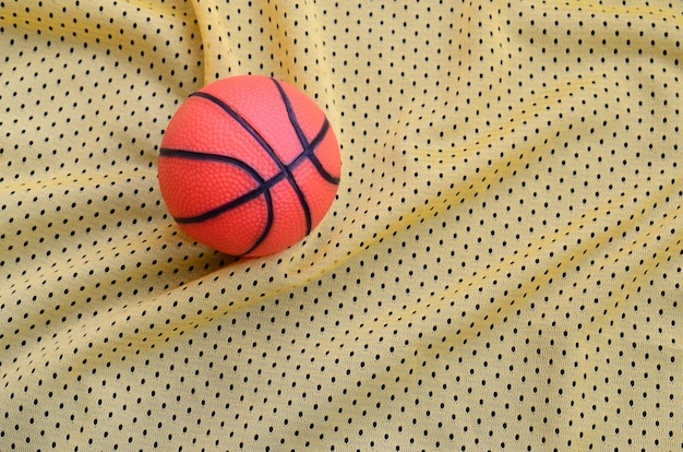Kleiner orange gummibasketball liegt auf einer gelben sportjerseykleidungsgewebebeschaffenheit und -hintergrund mit vielen falten