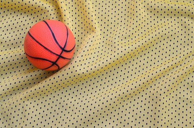 Kleiner orangefarbener gummibasketball liegt auf einem gelben trikot