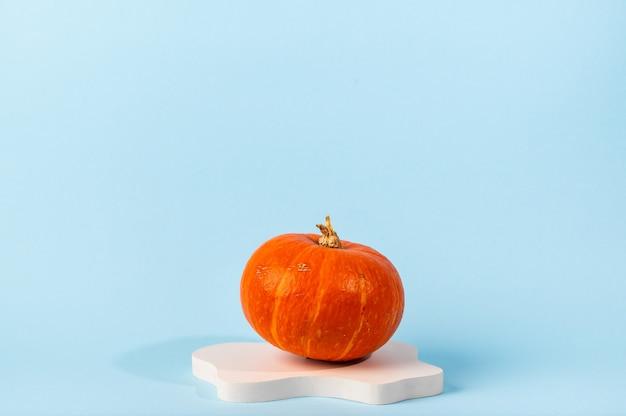Kleiner orangefarbener kürbis auf blauem hintergrund mit kopienraum. konzeptfeier von halloween oder thanksgiving. kosmetik-podest für halloween. herbststillleben.