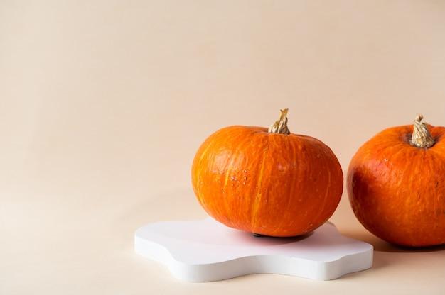 Kleiner orangefarbener kürbis auf pastellbeigem hintergrund mit kopienraum. konzeptfeier von halloween oder thanksgiving. kosmetik-podest für halloween. herbststillleben.
