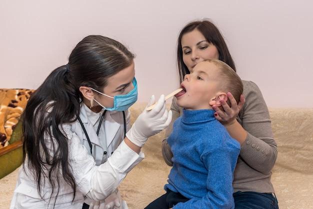 Kleiner patient zeigt dem kinderarzt seinen hals