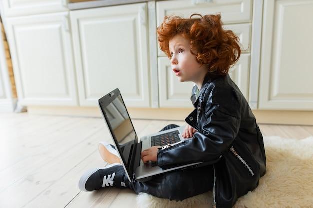 Kleiner redheadjunge benutzt einen laptop