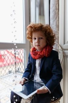 Kleiner redheadjunge benutzt einen tablette pc