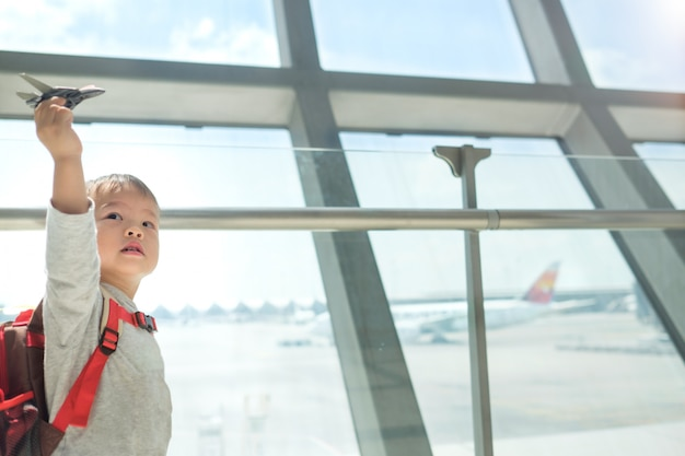 Kleiner reisender, asiatisches kind, das den spaß spielt mit flugzeug hat