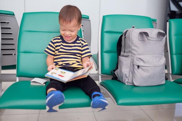 Kleiner reisender, niedliches lächelndes kleines asiatisches 30 monate / 2 jahre altes kleinkindjungenkind, das spaß hat, ein buch zu lesen, während auf seinen flug am gate im terminal am flughafen wartet, reisen mit kinderkonzept