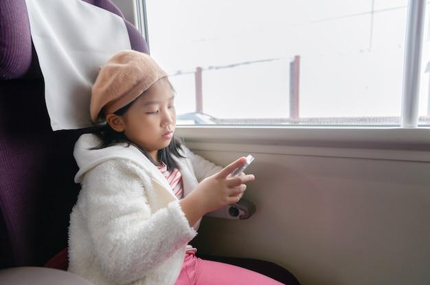 Kleiner reisender spielen handy im zug