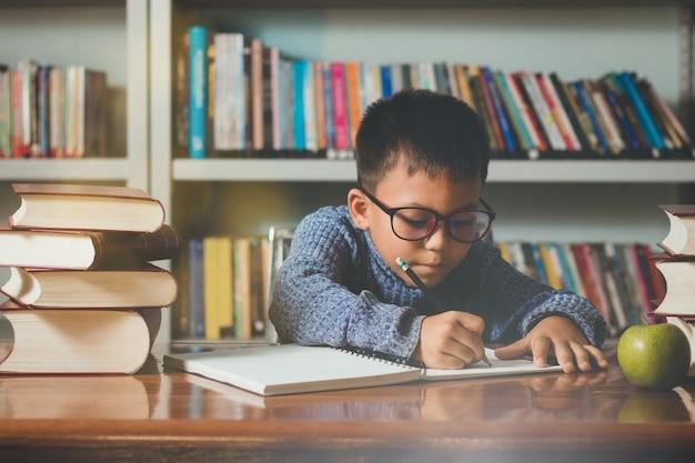 Kleiner reizender ausländerstudent, junge, der mit dem spaß, glücklich im klassenzimmer lernt.