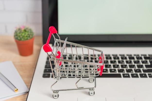 Kleiner roter einkaufswagen oder laufkatze auf laptoptastatur. technologie business online-shopping-konzept