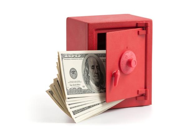 Kleiner roter safe mit offener tür und einem stapel dollarnoten