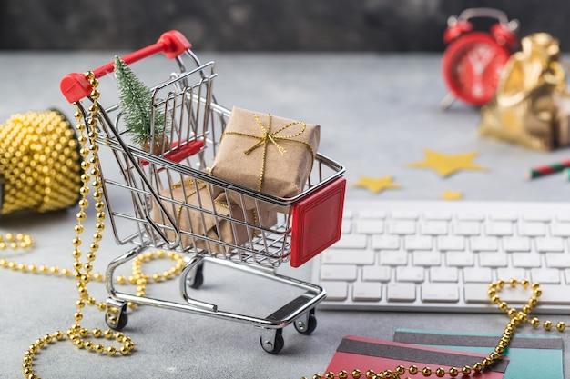 Kleiner roter warenkorb mit tastatur für internet-on-line-einkaufskonzept-weihnachtsgeschenke