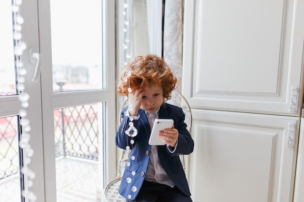 Kleiner rothaarigejunge benutzt einen smartphone, der zu hause in seinem raum sitzt