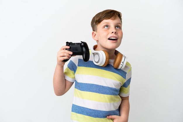 Kleiner rothaariger junge, der ein gamepad isoliert auf weißem hintergrund hält und nach oben schaut und mit überraschtem ausdruck