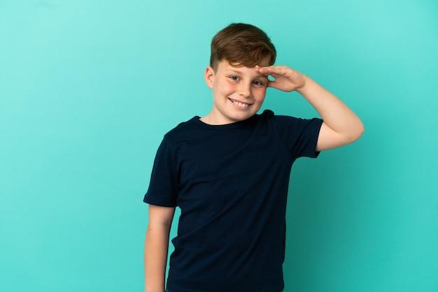 Kleiner rothaariger junge isoliert auf blauem hintergrund, der mit der hand mit glücklichem ausdruck grüßt