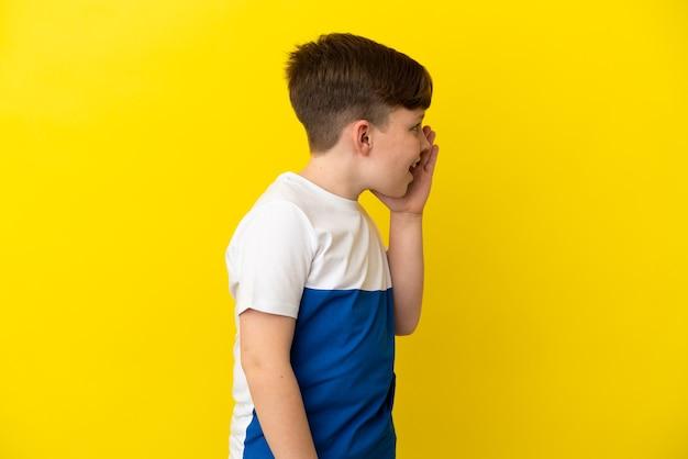 Kleiner rothaariger junge isoliert auf gelbem hintergrund, der mit weit geöffnetem mund zur seite schreit