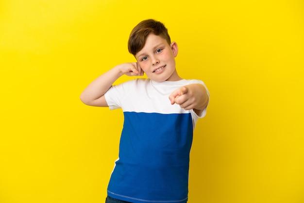 Kleiner rothaariger junge isoliert auf gelbem hintergrund, der telefongeste macht und nach vorne zeigt