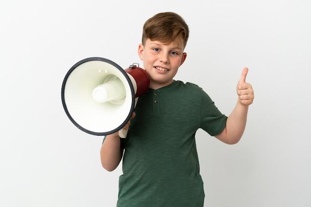Kleiner rothaariger junge isoliert auf weißem hintergrund, der ein megaphon mit dem daumen nach oben hält