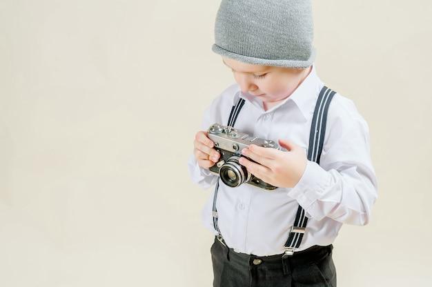 Kleiner rothaariger junge mit einer retro- kamera in den händen auf einem lokalisierten hellen hintergrund