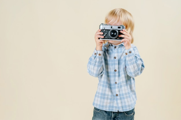 Kleiner rothaariger junge mit einer retro- kamera in den händen auf lokalisiert