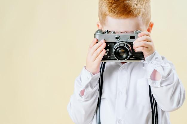 Kleiner rothaariger junge mit einer retro- kamera in den händen