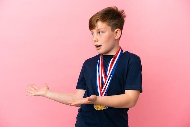 Kleiner rothaariger junge mit medaillen isoliert auf rosa hintergrund mit überraschendem gesichtsausdruck