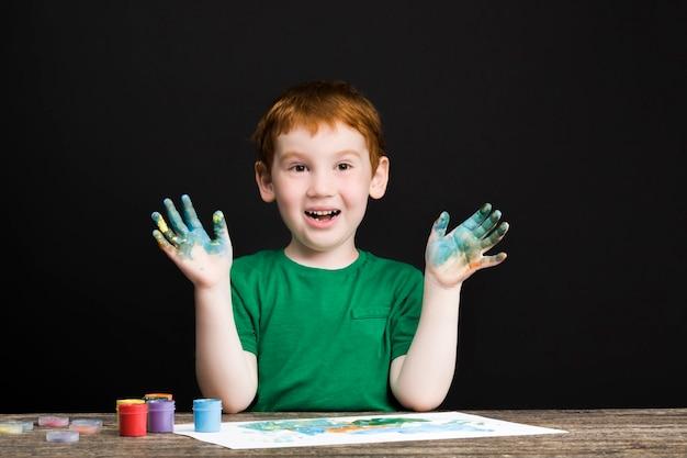 Kleiner rothaariger junge zeichnet auf papier mit farben in verschiedenen farben, der junge zeichnet mit seinen händen und so sind seine hände in farbe, blau, rot und anderen farben