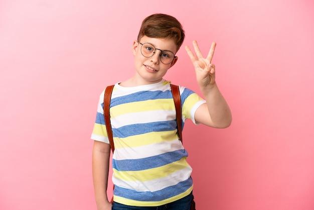 Kleiner rothaariger kaukasischer junge isoliert auf rosa hintergrund glücklich und zählt drei mit den fingern