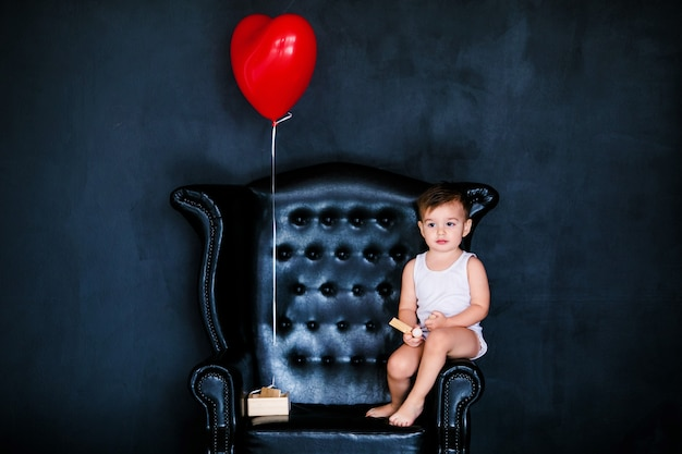 Kleiner säuglingsjunge 2 jahre alt im weißen t-shirt, das auf dem lehnsessel mit rotem herzballon sitzt
