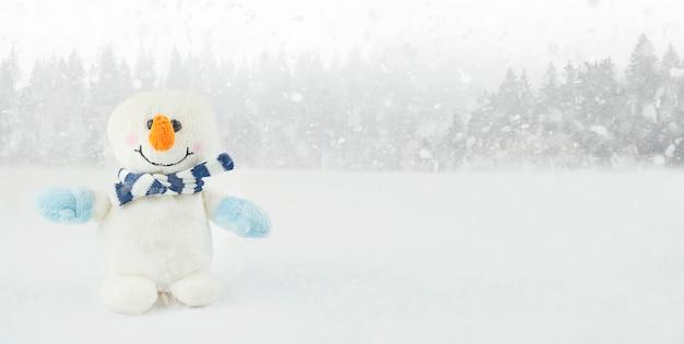 Kleiner schneemann auf einem winterhintergrund mit kopienraum. weihnachtshintergrund. neujahrskarte. banner.