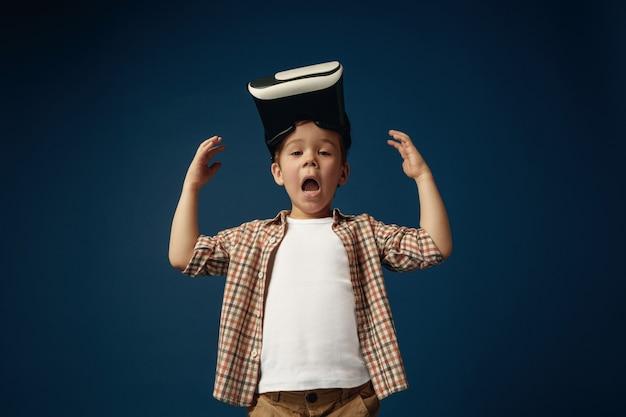 Kleiner schockierter junge, der hemd mit virtual-reality-headset trägt