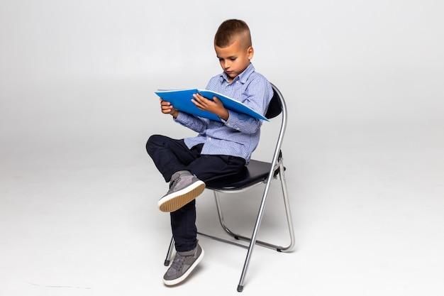 Kleiner schuljunge, der auf stuhl sitzt und notizbuch lokalisiert auf weißer wand liest