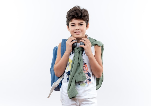 Kleiner schuljunge, der rückentasche und kopfhörer trägt und hand auf kopfhörer lokalisiert auf weißem hintergrund setzt
