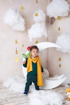 Kleiner schwarzer junge mit einer rose. herzlichen glückwunsch zum urlaub. kinderphantasie. kleiner lockiger afroamerikaner. urlaubskonzept.