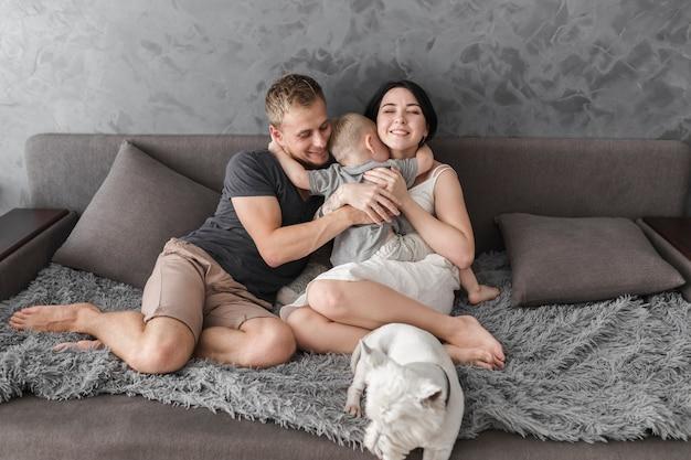 Kleiner sohn, der ihre eltern umarmt, auf sofa mit weißem hund zu sitzen