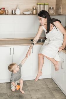Kleiner sohn, der seine mutter sitzt auf küchenarbeitsplatte zieht
