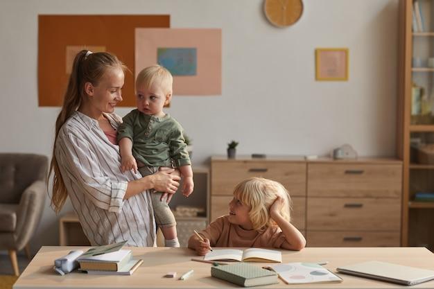 Kleiner sohn macht hausaufgaben am tisch mit seiner mutter, die ein kind in der hand hält und mit ihm im zimmer spricht