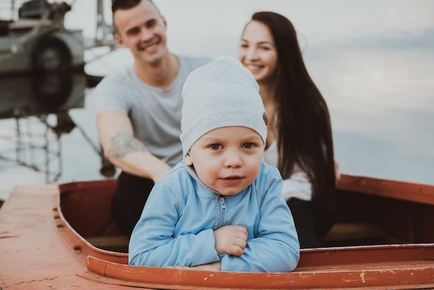 Kleiner sohn und ein glückliches paar eltern sitzen im sommer in einem boot am wasser